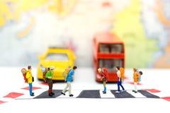 Miniaturleute: Reisendzebrastreifen die Straße auf den Stadtstraßen Bildgebrauch für Respekt für Verkehrsregeln, Reisekonzept Lizenzfreie Stockfotos