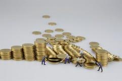 Miniaturleute sind zerstörter Stapel von Goldmünzen lizenzfreie stockfotografie