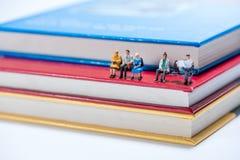 Miniaturleute stellen das Sitzen auf Stapel des Buches dar Stockfotografie