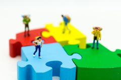 Miniaturleute: Tourist, der auf bunte Puzzlespiele geht Bildgebrauch für das Reisen in verschiedene Plätze, Reisekonzept Lizenzfreie Stockfotografie