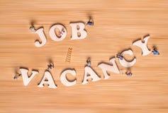 Miniaturleute und die Phrase Job Vacancy Kreatives Konzept lizenzfreies stockbild