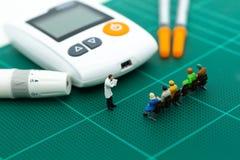 Miniaturleute- und Glukosemeter mit Lanzette Bildgebrauch für Medizin, Diabetes, Gesundheitswesenkonzept Stockbild