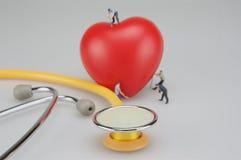 Miniaturleute und rotes Herz nahe Stethoskop stockfoto