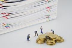 Miniaturleute und Stapel überbelasten Dokument mit Goldmünzen lizenzfreies stockbild