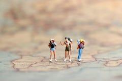Miniaturleute: Wanderer auf Weltkarte, Konzept der Reise Lizenzfreie Stockbilder