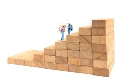 Miniaturleute: Wanderer, der auf hölzernem Block steht Lizenzfreies Stockbild