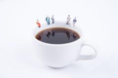 Miniaturleutegeschäftsteam, das auf weißer Kaffeetasse sitzt Stockfotos