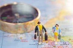 Miniaturleutereisender, der auf der Weltkarte steht Lizenzfreies Stockfoto
