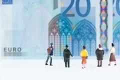 Miniaturmänner und Frauen, die den Hintergrund mit 20 Eurobanknoten betrachten Lizenzfreie Stockfotos