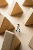 Miniaturmann, der Foto mit hölzernem Block des Dreiecks macht Stockbilder