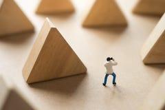 Miniaturmann, der Foto mit hölzernem Block des Dreiecks macht Stockfoto