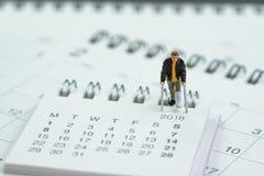 Miniaturmann des gebrochenen Beines der leute, der auf Kalender unter Verwendung als Ba steht Lizenzfreie Stockbilder