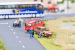 Miniaturmechaniker, die einen durchbohrten Reifen weg von der Fahrbahn ersetzen Stockfotografie