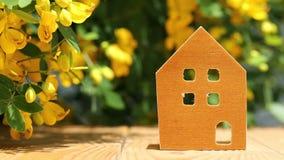 Miniaturmodell des Hauses mit Blumenhintergrund stock video footage