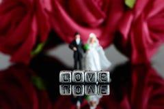 Miniaturmodellbauhochzeitspaare mit dem Wort lieben auf Perlen und rosafarbenem Blumenstrauß Lizenzfreies Stockbild