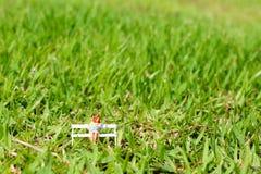Miniaturmutter und Kind, die auf der Bank im Garten umgeben durch grünes Gras sitzt Stockfotografie