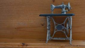 Miniaturnähmaschine gegen hölzernen Hintergrund Stockbild