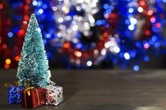 Miniaturowa choinka z mini boże narodzenie prezentami na trzy kolorów bokeh tle Obrazy Royalty Free