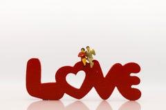 Miniaturowa para, siedzi na miłość tekscie jest drewnianym czerwonym kolorem, używać jako miłość dwa ludzie, valentine pojęcie Zdjęcie Stock