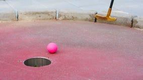 Miniaturowa piłka golfowa tuż przed spadać w miniaturowego golfa dziurę obraz royalty free