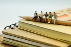 Miniaturowa postać: Ludzie siedzi na stercie notatnik one obrazy stock