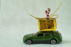Miniaturowa postaci Santa Claus pozycja na dużym teraźniejszości pudełku na samochodzie Obraz Stock