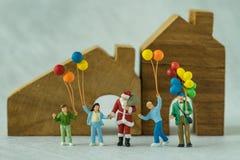 Miniaturowa postaci Santa Claus pozycja z szczęśliwymi rodzinnymi ludźmi h zdjęcie royalty free