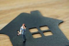 Miniaturowa szczęśliwa rodzinna postaci pozycja na papieru domu jako propert Zdjęcie Royalty Free