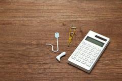 Miniaturowe rzeczy choroba lub uraz obok kalkulatora zdjęcia royalty free