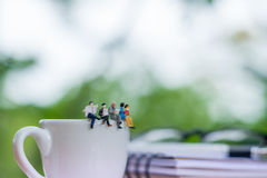 Miniaturowi businessmans readinging książkę na filiżance kawy obraz stock