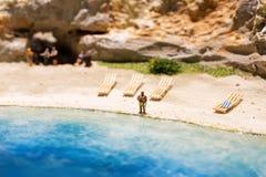 Miniaturowi ludzie: śmieszna z nadwagą afro amerykańska mężczyzna pozycja przy plażą Styl życia, urlopowy pojęcie Zdjęcia Stock