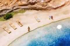 Miniaturowi ludzie: śmieszna z nadwagą afro amerykańska mężczyzna pozycja przy plażą Styl życia, urlopowy pojęcie Obraz Stock