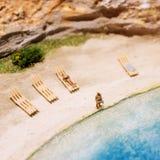 Miniaturowi ludzie: śmieszna z nadwagą afro amerykańska mężczyzna pozycja przy plażą Styl życia, urlopowy pojęcie Fotografia Stock