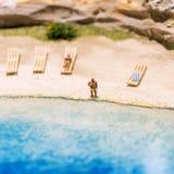 Miniaturowi ludzie: śmieszna z nadwagą afro amerykańska mężczyzna pozycja przy plażą Styl życia, urlopowy pojęcie Zdjęcie Stock