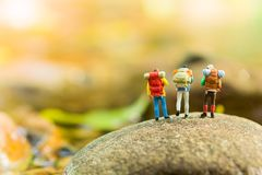 Miniaturowi ludzie, backpackers chodzi na kamieniach przy rzeką Podróż stylu życia przygody wakacji pojęcie Zdjęcie Royalty Free
