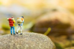 Miniaturowi ludzie, backpackers chodzi na kamieniach przy rzeką Podróż stylu życia przygody wakacji pojęcie Obrazy Royalty Free