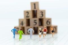 Miniaturowi ludzie biega sterta numerowy drewniany blok Wizerunku use dla zdrowego, ćwiczenia pojęcie Obrazy Royalty Free