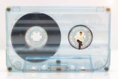 Miniaturowi ludzie: Biznesmen czytelnicza gazeta na taśmy kasecie zdjęcia stock
