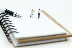 Miniaturowi ludzie: Biznesmen pozycja na biel notatce i piórze Wizerunku use dla pisze tekscie na papierze fotografia royalty free