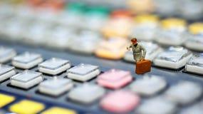 Miniaturowi ludzie: biznesowy mężczyzna patrzeje zegarek i spacer na obraz royalty free