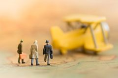 Miniaturowi ludzie biznesu: biznesy zespalają się czekanie dla samolotu na światowej mapie Fotografia Stock