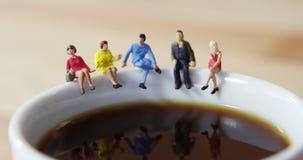 Miniaturowi ludzie biznesu siedzi na krawędzi filiżanki zbiory wideo