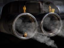 Miniaturowi ludzie egzamininuje samochód rurę wydechową fotografia royalty free