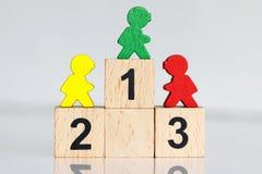 Miniaturowi ludzie: kolorowe postacie stoi na drewnianym podium 1,2,3 z biznes drużyną obrazy royalty free