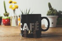 Miniaturowi ludzie maluje kawowego kubek Fotografia Royalty Free
