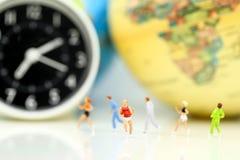 Miniaturowi ludzie: maratonów biegacze z zegarową i światową mapą, jo zdjęcie royalty free