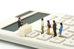 Miniaturowi ludzie Płacą kolejka rocznego dochodu podatek dla roku na kalkulatorze używać jako tła biznesowy pojęcie i finanse co obrazy royalty free