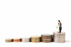 Miniaturowi ludzie poślubia na stert monetach na białym tle Zdjęcie Royalty Free