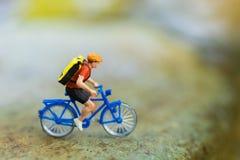 Miniaturowi ludzie: Podróżnicy jedzie bicykl na niewygładzonej drodze używać jako tło podróżni biznesowi pojęcia Fotografia Royalty Free