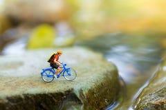 Miniaturowi ludzie: Podróżnicy jedzie bicykl na niewygładzonej drodze używać jako tło podróżni biznesowi pojęcia Obraz Stock